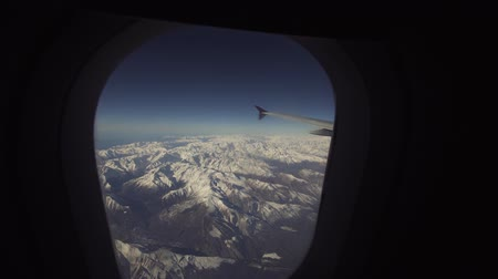 samolot : Mountain range with snow from the airplane window. Airplane wing. Aerial view on snowy mountains through window of an aircraft. Travel concept.