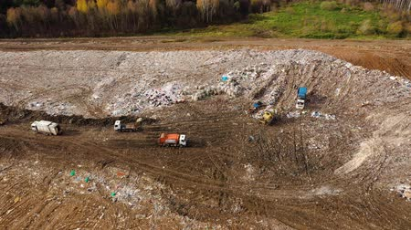 уродливый : Landfill. A huge pile of garbage surrounded by forest. Garbage trucks carry garbage to a landfill, top view.