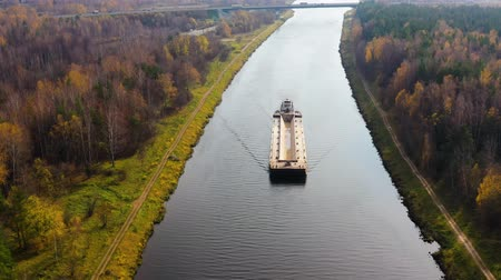 vnitrozemí : River tug with a barge view from above. River channel for freight transportation, top view. Beautiful landscape with a wide river and autumn forest. Dostupné videozáznamy