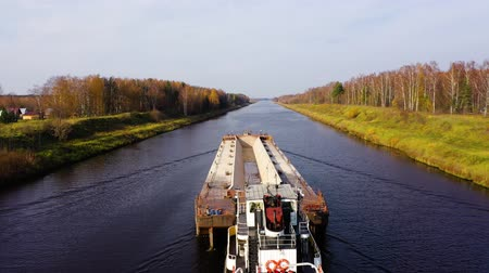remorqueur : Aerial view of River tug with a barge. River channel for freight transportation, top view. Beautiful landscape with a wide river and autumn forest.