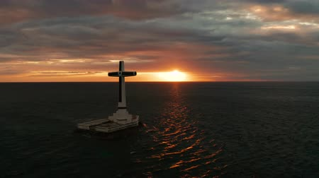 crucifixo : Catholic cross in sunken cemetery in the sea at sunset, aerial drone. colorful sky during the sunset. Large crucafix marking the underwater sunken cemetary, Camiguin Island Philippines.