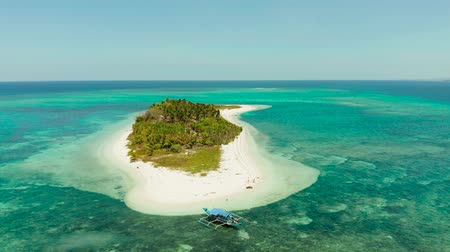 island hopping : Travel concept: tropical island on an atoll with beautiful sandy beach by coral reef from above. Canimeran Island and coral reef. Summer and travel vacation concept.