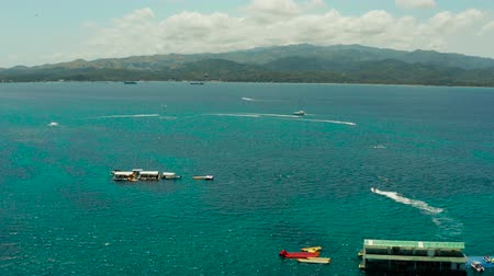 People flying on a colorful parachute towed by a motor boat, aerial view. Parasailing in blue sky. Vídeos
