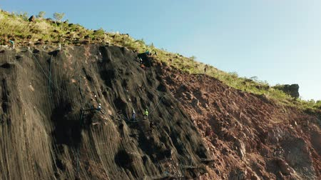 landslide : Protection of road from mountain slough, rockfall with metal accumulative restraining net fences. Workers constructing anti-landslide concrete wall prevent protect against rock slides. Rockfall protection. Workers strengthen the slope of the mountain with Stock Footage