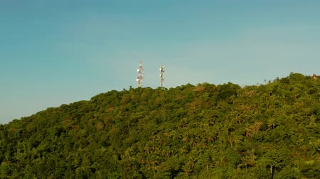 reflektör : Telecommunication tower, communication antenna in mountains and rainforest, aerial view. Repeaters on a metal tower. Boracay, Philippines