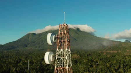 передавать : Antennas and microwaves link dishes of mobile phone network and TV transmitter on telecommunication towers with mountains and rainforest. Camiguin, Philippines