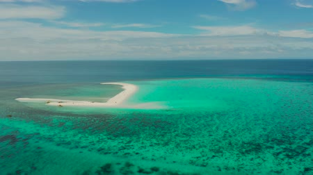 island hopping : Tropical island and sandy beach with tourists surrounded by coral reef and blue sea, aerial view. Sandbar Atoll. Island with sand bar and coral reef. Summer and travel vacation concept, Camiguin, Philippines. Stock Footage