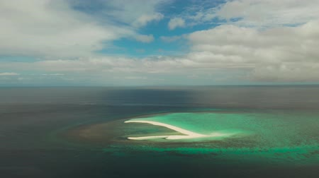 island hopping : Tropical white island and sandy beach with tourists surrounded by coral reef and blue sea, aerial view. Sandbar Atoll. Island with sand bar and coral reef. Summer and travel vacation concept, Camiguin, Philippines. Stock Footage