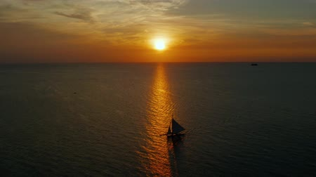 yansıyan : Sunset above the sea surface with sailing yachts, aerial view Boracay, Philippines. Reflected sun on a water surface. Sunset over ocean. Seascape, Summer and travel vacation concept Stok Video
