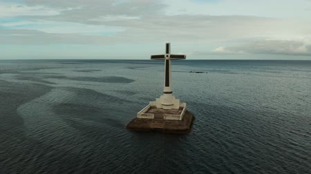 crucifixo : Catholic cross in sunken cemetery in the sea at sunset, aerial view. Sunset at Sunken Cemetery Camiguin Island Philippines.