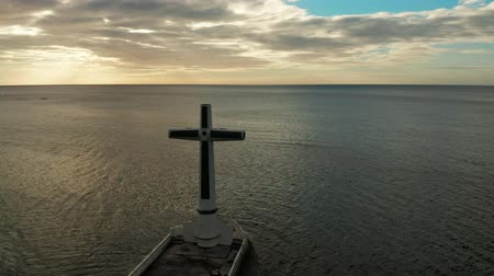 crucifixo : Catholic cross in sunken cemetery in the sea at sunset, aerial drone. Large crucafix marking the underwater sunken cemetary, Camiguin Island Philippines. Stock Footage
