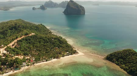 Aerial view tropical sandy beach and blue water. Las Cabanas, El Nido, Palawan, Philippines. Seascape with sea, sand, palm trees. Summer and travel vacation concept