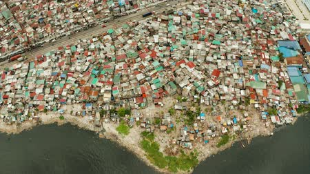 Slums with shacks of local residents and the river bank littered with garbage from above. Manila, Philippines. Archivo de Video