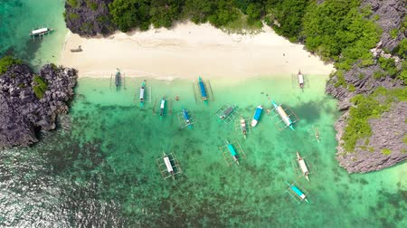 Sandy beach with tourists and tropical island by atoll with coral reef, top view. Matukad Island, Caramoan Islands, Philippines. Summer and travel vacation concept. Boats and tourists on the beach.
