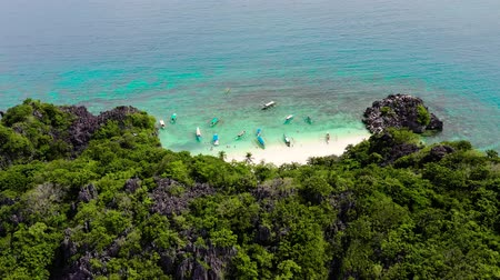 laguna : Tropical landscape: Matukad Island with beautiful beach and tourists by turquoise water view from above. Caramoan Islands, Philippines. Summer and travel vacation concept. Tropical island with a white sandy beach.