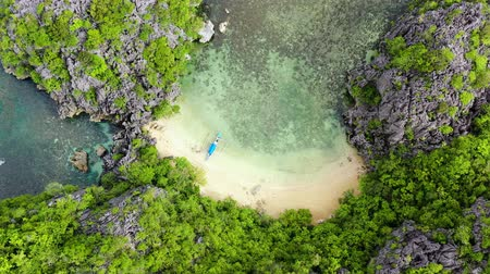 island hopping : Tropical island on the atoll and turquoise lagoon. Rocky island with white sandy beach, aerial view. Caramoan Islands, Philippines.
