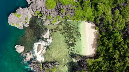 Sandy beach with tourists and tropical island by atoll with coral reef, top view. Matukad Island, Caramoan Islands, Philippines. Summer and travel vacation concept. Rocky island with a small beach. Archivo de Video