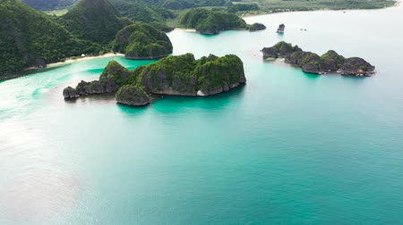 island hopping : Tropical islands and blue sea, aerial drone. Caramoan Islands, Philippines. Rocky islands with trees.