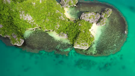 island hopping : Tropical islands and blue sea, aerial view . Caramoan Islands, Philippines. Rocky islands with trees. Summer and travel vacation concept. Rocky island with rainforest Stock Footage