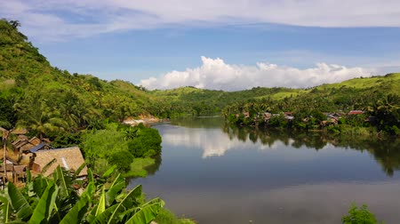 tropikal iklim : Tropical landscape in sunny weather. Village by the river. Green hills and river. Summer and travel vacation concept. The nature of the Philippine Islands.