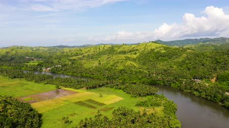 hamlet : River and green hills. Beautiful natural scenery of river in southeast Asia. Countryside on a large tropical island. Small village on the green hills by the river. The nature of the Philippines.