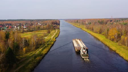 vnitrozemí : River tug with a barge. River channel for freight transportation, top view. Beautiful landscape with a wide river and autumn forest. Dostupné videozáznamy
