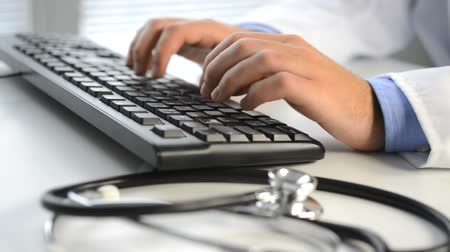 сообщить : closeup of male doctor hands typing on keyboard Стоковые видеозаписи