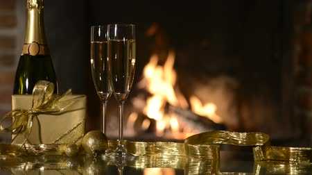 šampaňské : Two champagne glasses and gift boxes in front of fireplace