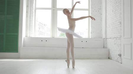 bale : Attractive ballerina in white gown is practicing in the classroom. She does a step forward and makes an arabesque position. Then she is making some small steps in her pointes and spinning around. These steps are full of grace and beauty Stok Video