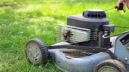 bagger : a lawn mower is standing on the grass, on a green lawn, a man starts a lawn mower Stock Footage