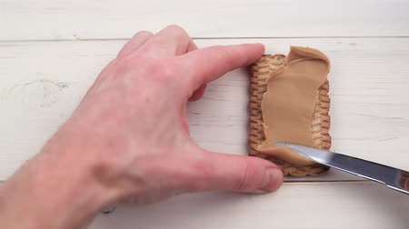 peanut butter paste with a knife spread on cookies