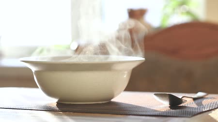 calor : Steam rises over a white ceramic plate on the kitchen table