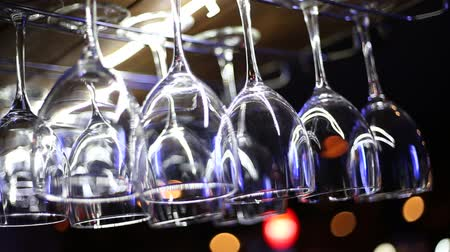 Clean wine glasses hang over the bar in a restaurant or in a nightclub