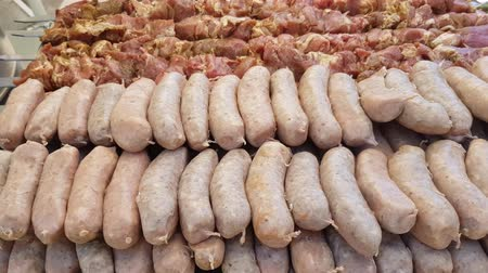 raw sausages and shish kebab. preparation for a large outdoor picnic. catering Stock Footage