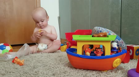 an infant boy in a diaper plays with toys on the floor. early development of children