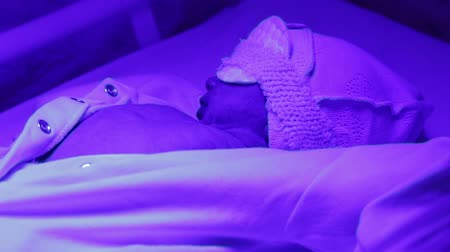 a baby with a blindfold is lying under the ultraviolet lamp. lechenie increased bilirubin in newborns
