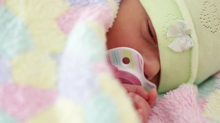 cobertor : A newborn in a hat and covered with a warm blanket, with a pacifier lying in bed
