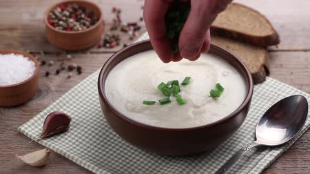 суп : white vegetable or mushroom soup in a plate. nearby are spices and bread Стоковые видеозаписи