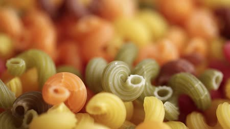 uncooked multi colored pasta as background. blurred focus