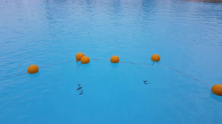 kék háttér : Red round restrictive buoys in the pool. safety tool during the rest on the water Stock mozgókép
