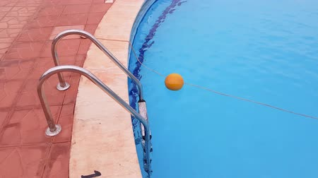 metal ladder to the pool. in the pool is clear blue water. water activities