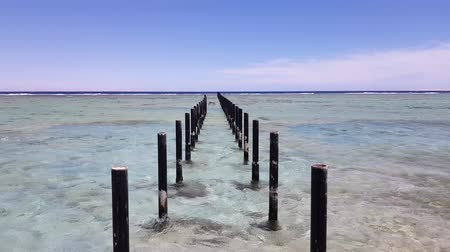 influenzy : piles for a bridge to the sea. cloudless blue sky on the horizon and calm clear sea Dostupné videozáznamy