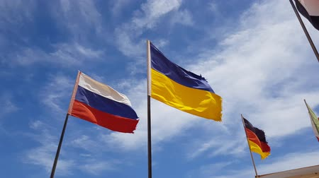 different flags flying. near are the flags of Ukraine and Russia against the sky