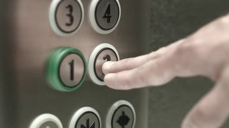 asansör : Man presses a button the 2 floor in an elevator. Close up shot
