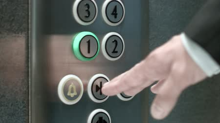 asansör : Man presses a button the first floor and a button closing elevator doors. Close up shot Stok Video