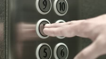 dígitos : Man presses a button the 7 floor in an elevator. Close up shot