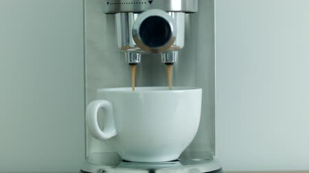 kahvehane : Making coffee using the coffee machine in a white cup
