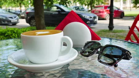 fresh coffee : White cup of coffee . Glasses are nearby the cup Stock Footage
