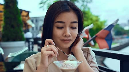 hipster : Portrait of a cute and gorgeous asian woman with ice cream sitting on a cafe terrace
