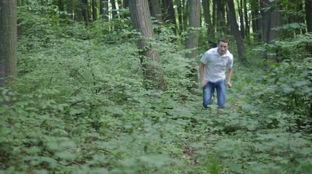 into focus : Two men chasing trough the woods Stock Footage